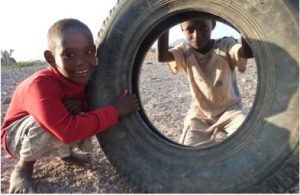 Boys play with a tire in the Horn of Africa